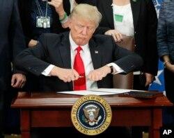 Donald Trump assinando um Decreto Lei quando tomou posse