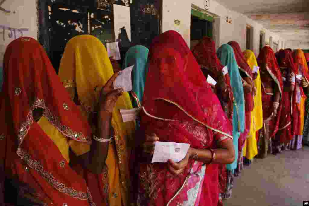 Indian village women line up outside a polling station to cast their votes during Rajasthan state assembly elections at Devnagar village near Ajmer.