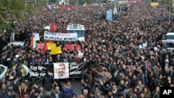 """Thousands of people march during the funeral of Tahir Elci, president of the Diyarbakir Bar Association and a leading human rights defender, in Diyarbakir, Turkey, Nov. 29, 2015. Elci was killed Saturday while making a press statement intended to call attention to damage done to the 1,500-year-old Four-Legged Minaret Mosque by recent clashes between Turkish security forces and Kurdistan Workers' Party militants. The banner in Turkish and Kurdish reads: """" We will not forget you."""""""