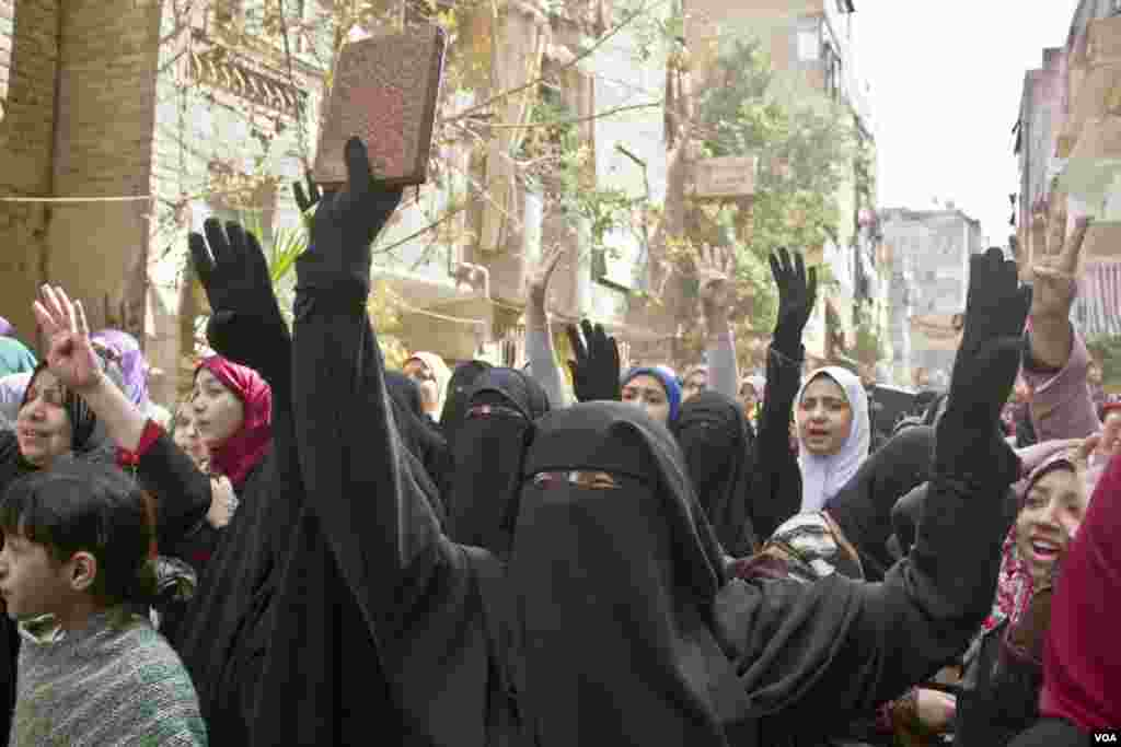 Protesters flash the four finger sign representing Rabaa, which was the location in Cairo that saw the most intense violence six months ago, as they march in Cairo on Feb. 14, 2014. (Hamada Elrasam/VOA)