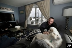 Denis Champagne, Jr. plays with his dogs Maebelle and Isabel at home near the coast in Salisbury, Mass., Jan. 23, 2019.