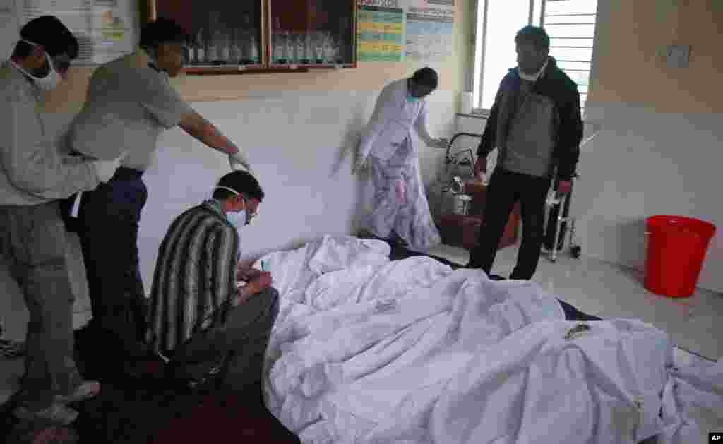Medical staff inspect the bodies of victims at a hospital in Ghodegaon village in the western Indian state of Maharashtra, Wednesday, July 30, 2014