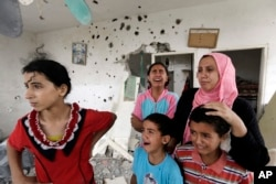 Palestinian Salwa Shabat, right, accompanied by some of her children, from left to right, Amira, Huda, top, Ahmed and Anas, weep as they inspect the damage upon returning to the family house, destroyed by Israeli strikes in the town of Beit Hanoun.