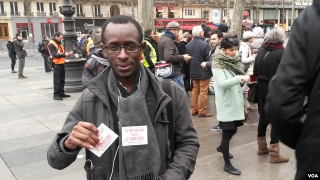 Slimane Tirera passing out anti-discrimination flyers. (Lisa Bryant/VOA)