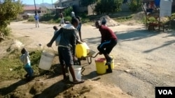 Some Mutare residents collecting water from a burst pipe following the disconnection of water supplies at their homes.
