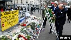 Menlu AS John Kerry (kiri) didampingi Menlu Perancis Laurent Fabius di lokasi serangan teror di supermarket Yahudi di Paris (16/1).