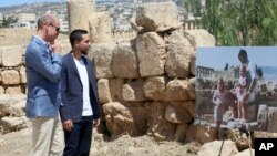 Britain's Prince William and Jordanian Crown Prince Hussein look at a photograph showing William's wife, the former Kate Middleton, her father Michael and younger sister Pippa in the ruins of the Roman city of Jerash in the 1980s in Jerash, Jordan, June 2