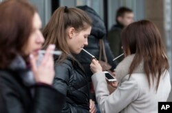 Women smoke cigarettes at a shopping center in Moscow, Russia, Tuesday, Feb. 12, 2013.