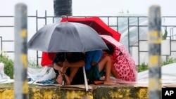 Warga berlindung di balik paying mereka sementara angin kencang dan hujan turun akibat Topan Koppu, 18 Oktober 2015 di Manila, Filipina.