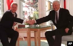 FILE - U.S. President Bill Clinton and Russian President Boris Yeltsin shake hands at the Mantyniemi presidential residence on the outskirts of Helsinki, March 21, 1997, on the second day of their two-day summit.
