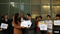 香港和平佔中發起人朱耀明(後排右一)與戴耀廷(前排左二)及十多位團體代表,到政府總部向港府代表遞交政改諮詢民意資料。(美國之音湯惠芸攝)