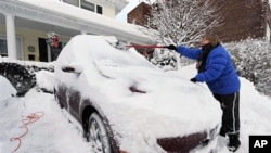 A woman shovels snow off her car in a driveway in Port Washington, New York, Jan 27 2011