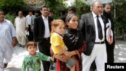 FILE - Khalida Bibi, center, sister of Farzana Iqbal, walks with her lawyer as she arrives at a court in Lahore for the trial of those implicated in Iqbal's death, June 2, 2014.