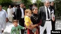 Khalida Bibi (tengah), saudara perempuan Farzana Iqbal, didampingi pengacara saat tiba di pengadilan Lahore untuk sidang para tersangka pembunuhan adiknya, Juni 2014.