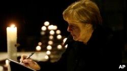 앙겔라 메르켈 독일 총리가20일 베를린 트럭 테러 희생자 추모 장소인 교회 방문록에 기록하고 있다.