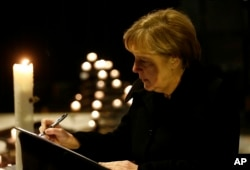 German Chancellor Angela Merkel signs the condolence book at the Memorial Church in Berlin, Germany, Dec. 20, 2016, one day after a truck ran into a crowded Christmas market in Berlin and killed several people.