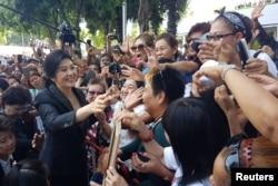 លោកស្រី Yingluck Shinawatra អតីតនាយករដ្ឋមន្ត្រីថៃស្វាគមន៍អ្នកគាំទ្រ នៅពេលលោកស្រីចាកចេញពីតុលាការកំពូលនៅក្នុងក្រុងបាងកក ប្រទេសថៃ កាលពីថ្ងៃទី១ ខែសីហា ឆ្នាំ២០១៧។