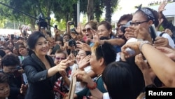 FILE -Ousted former Thai Prime Minister Yingluck Shinawatra greets supporters as she leaves the Supreme Court in Bangkok, Thailand, Aug. 1, 2017.