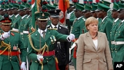 German Chancellor, Angela Merkel, center, inspects a guard of honor, during her visit to the state house, in Abuja, Nigeria.