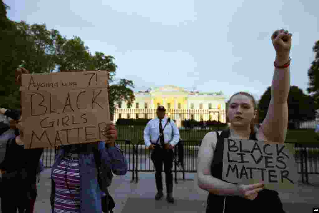 Protestors hold signs in front of the White House during a protest to support the rallies in Baltimore, April 29, 2015.