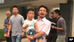 This image taken from video shows Chinese labor activists Hua Haifeng, center, carrying his son, Bobo, and Li Zhao, second from left, leaving a police station after being released in Ganzhou in southern China's Jiangxi province, June 28, 2017. Chinese authorities have released three activists, including Hua and Li, who had been detained after investigating labor conditions at a factory that produced shoes for Ivanka Trump and other brands.