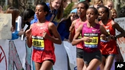 FILE - Buzunesh Deba, left, of Ethiopia, runs in a group of elite female participants past Wellesley College during the 118th Boston Marathon in Wellesley, Mass., April 21, 2014.
