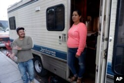 Delmi Ruiz, right, and her husband Benito Hernandez chat outside their RV where their family lives and sleeps, Oct. 5, 2017, in Mountain View, California.