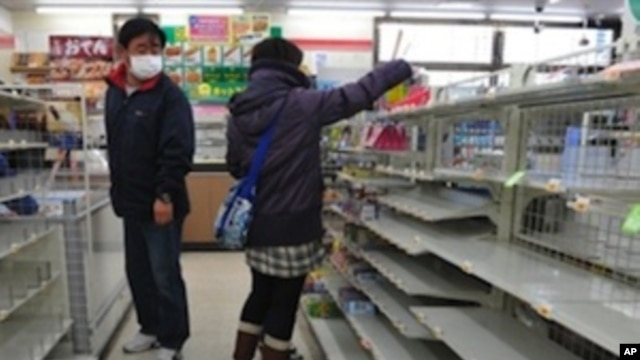 People look for food amid empty shelves in a shop in Fukushima on March 13, 2011.