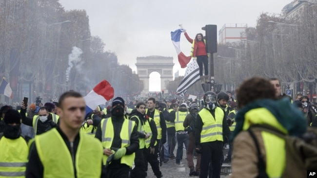 Los manifestantes marchan en la famosa avenida Campos Elíseos, en París, Francia, mientras protestan por el alza de los precios del combustible el 24 de noviembre de 2018.
