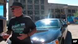 """Limousine tour guide Harold Davis is dressed as """"Breaking Bad"""" character Walter White, as Albuquerque tourists officials get ready for an event celebrating the premiere of the final season of AMC's TV series, Aug. 9, 2013."""