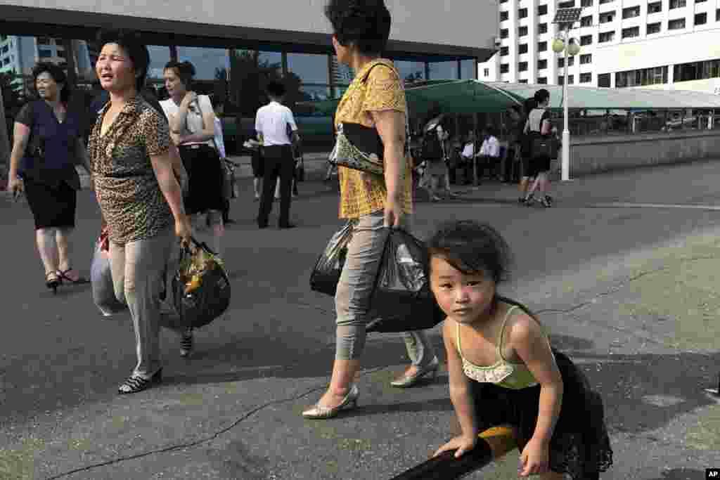 평양의 한 백화점 앞, 장바구니를 든 여성들 옆에서 혼자 놀던 소녀가 사진기자를 바라보고 있다.