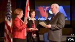 美國之音新台長阿曼達·貝內特(Amanda Bennett,左)一手放在家傳的聖經上宣誓就職(2016年4月18日)