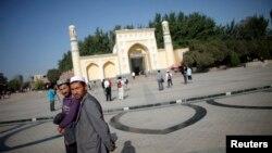 Warga Uighur berjalan di depan masjid di Kashgar, propinsi Xinjiang (Foto: dok). Pengadilan di daerah ini dilaporkan telah menjatuhkan hukuman penjara atas 19 warga Uighur dengan tuduhan menghasut ekstrimisme agama.