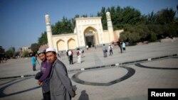 Người Uighur đi bộ bên ngoài một nhà thờ Hồi giáo ở Kashgar, Tân Cương.