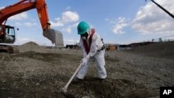 A worker, wearing a protective suit and a mask, levels ground at the tsunami-crippled Fukushima Dai-ichi nuclear power plant, operated by Tokyo Electric Power Co. (TEPCO), in Okuma, Fukushima Prefecture, northeastern Japan, Wednesday, Feb. 10, 2016.