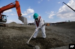 FILE - A worker, wearing a protective suit and a mask, levels ground at the tsunami-crippled Fukushima Dai-ichi nuclear power plant, operated by Tokyo Electric Power Co. (TEPCO), in Okuma, Fukushima Prefecture, northeastern Japan, Feb. 10, 2016.