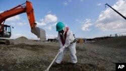 Seorang pekerja mengenakan pakaian pelindung dan masker, memeriksa PLTN Dai-ichi di Fukushima yang dioperasikan oleh TEPCO di Okuma, Fukushima (10/2).