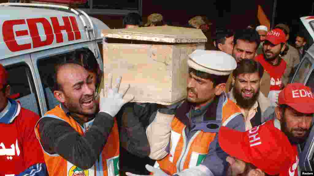 Rescue workers and family members carry the coffin of a student, who was killed during an attack by Taliban gunmen on a school in Peshawar, Pakistan, Dec. 16, 2014.