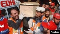 Rescue workers and family members carry the coffin of a student, who killed during an attack by Taliban gunmen on the Army Public School, in Peshawar, Dec. 16, 2014. (REUTERS/Khuram Parvez)