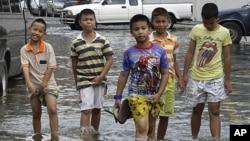 泰國小童在遭水掩的曼谷街頭過路﹐泰國政府已經準備排洪。