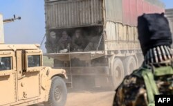 FILE - A truck carries men identified as Islamic State group fighters who surrendered to Kurdish-led Syrian Democratic Forces (SDF) as they are transported out of IS's last holdout of Baghuz, Syria, Feb. 20, 2019.
