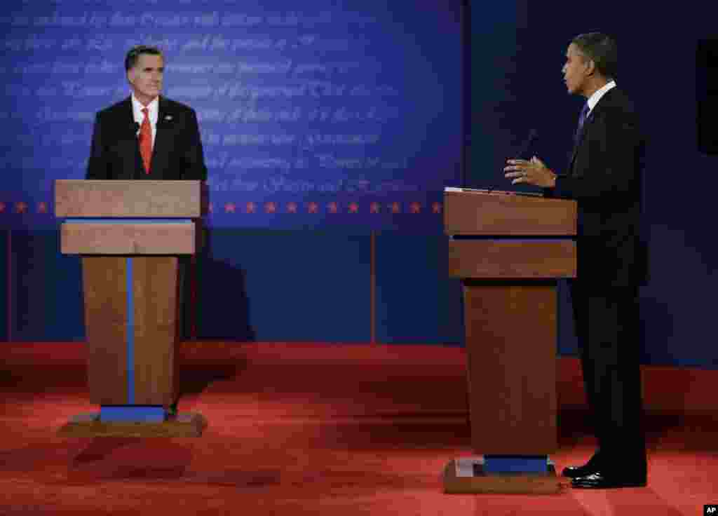 Republican presidential candidate Mitt Romney, left, listens to President Barack Obama during the first presidential debate at the University of Denver.