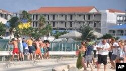 Du khách tắm biển đứng cạnh hàng rào xem máy bay cất cánh và hạ cánh tại sân bay Princess Juliana trên đảo St. Maarten của Hà Lan ở Caribe. Mặc dù có nhiều cảnh báo về sự nguy hiểm từ lực đẩy phản lực của động cơ máy bay nhưng khách du lịch vẫn thích đến gần để cảm nhận nó.