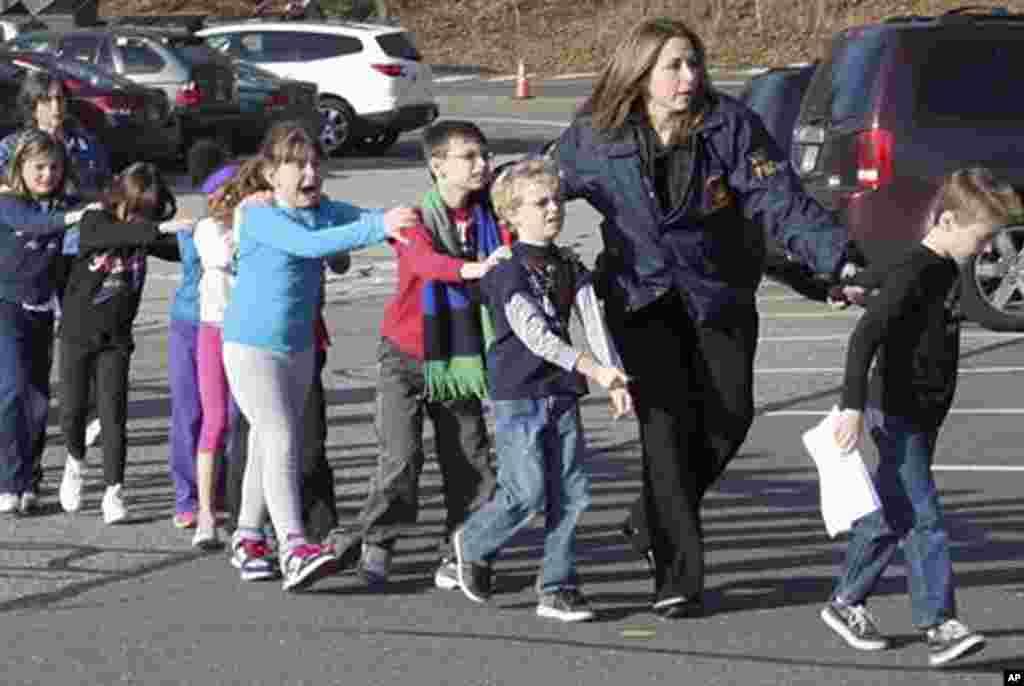 პოლიციას სკოლის მოსწავლეები სროლის შემდეგ უსაფრთხო ადგილას გადაყავს. 14 დეკემბერი, 2012.