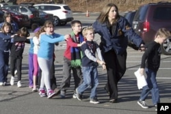 FILE - In this photo provided by the Newtown Bee, Connecticut State Police lead children from the Sandy Hook Elementary School in Newtown, Conn., following a reported shooting there, Dec. 14, 2012.
