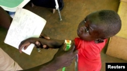FILE - A Congolese boy has his arm measured for malnutrition in a clinic, March 18, 2006.