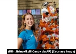 Here, Alina Morse stands next to her creation, a decorated tree for Halloween. (Klint Briney/Zolli Candy via AP)