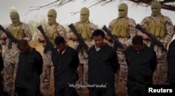 FILE - Militants from the so-called Islamic State stand behind what are said to be Ethiopian Christians in Libya, in this still image from an undated video posted to a social media website on April 19, 2015.