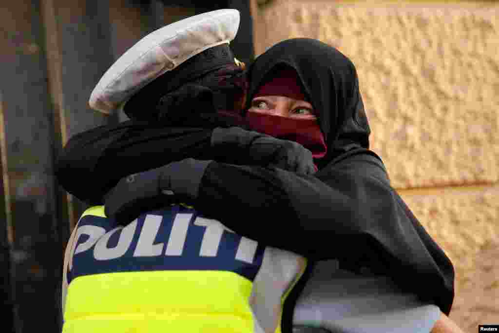 Ayah, 37, wearing a niqab, weeps as she is embraced by a Danish police officer during a demonstration against a ban on the face veil, in Copenhagen, Denmark, Aug. 1, 2018.