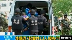 FILE - Riot policemen lead men who are about to be executed into a police van in an unknown location in the Xinjiang Uighur Autonomous Region.